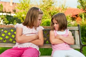Small girls (sisters) siting on bench offended after quarrel - outdoors in backyard